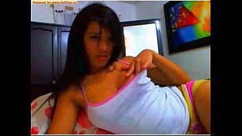 Novinha encantadora do sorriso lindo brincando no biquinho dos seios na webcam